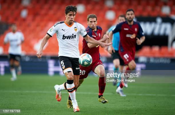 Gabriel Paulista of Valencia competes for the ball with Darko Brasanac of Osasuna during the Liga match between Valencia CF and CA Osasuna at Estadio...