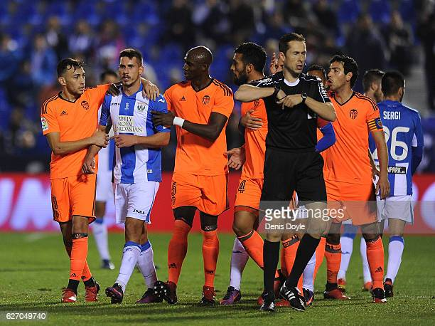 Gabriel Pires of CD Leganes is led away by Munir El Haddadi and Eliaquim Mangala of Valencia CF during the Copa del Rey Round of 32 match between CD...