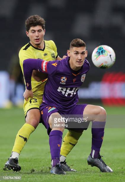 Gabriel Popovic of the Glory is challenged by Liberato Cacace of the Phoenix during the round 27 A-League match between the Perth Glory and the...