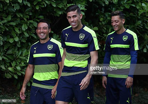 Gabriel Santi Cazorla and Mezut Ozil of Arsenal arrive during Arsenal training session ahead of their Champions League match against PSG at London...