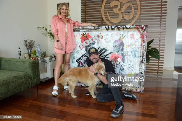 Gabriel Soto and Irina Baeva pose for photo with the work that the Mexican artist Abraham Cornejo gave them on March 27, 2021 in Mexico City, Mexico.