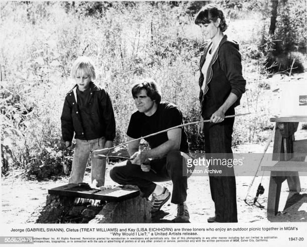 Gabriel Swann Treat Williams and Lisa Eichhorn roast hot dogs in a scene from the MGM movie Why Would I Lie circa 1980