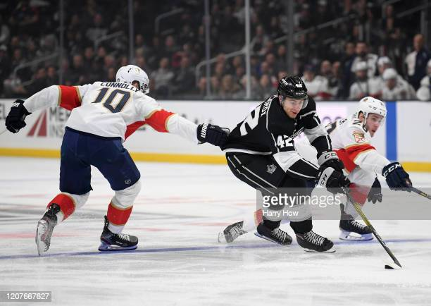 Gabriel Vilardi of the Los Angeles Kings stickhandles between Brett Connolly and Aleksi Saarela of the Florida Panthers during the second period at...