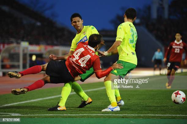 Gabriel Xavier of Nagoya Grampus is challenged by Andrew Kumagai and Kim Byeom Yong of JEF United Chiba during the JLeague J1 Promotion PlayOff semi...