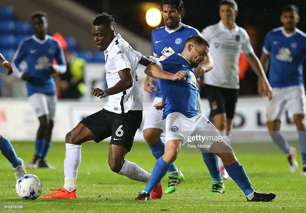 Gabriel Zakuani of Northampton Town plays the ball under pressure from Paul Taylor of Peterborough United during the Sky Bet League One match between Peterborough United and Northampton Town at ABAX Stadium on October 18, 2016 in Peterborough, England.