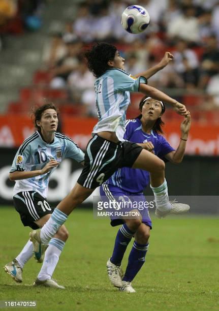 Gabriela Chavez of Argentina heads the ball as teamate Emilia Mendieta and Japanese player Yuki Nagasato looks on during their 2007 FIFA Women's...
