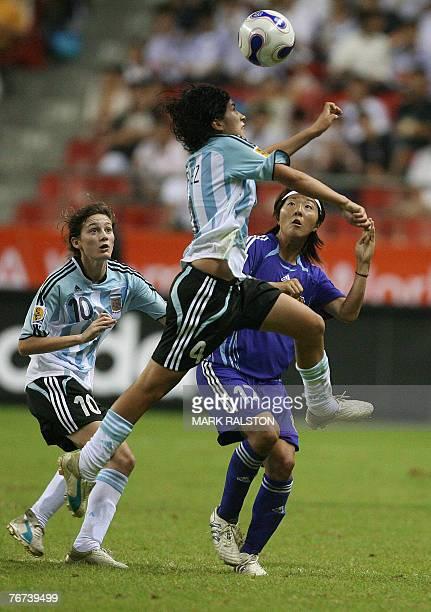 Gabriela Chavez of Argentina heads the ball as teammate Emilia Mendieta and Japanese player Yuki Nagasato looks on during their 2007 FIFA Women's...