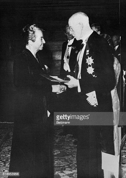 Gabriela Mistral , Chilean poet, receiving Nobel Prize from King Christian X of Denmark.