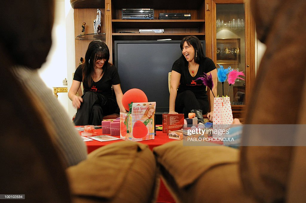Gabriela Perez (L) and Nicole Komin, representatives for Latin America of 'La Maleta Roja' (The Red Suitcase) company, promote sex toys in Montevideo, Uruguay, on May 15, 2010. The Spanish company, specializing in erotic toys, lingerie and cosmetics, sells its products through saleswomen who go to friends meetings at homes. AFP PHOTO/Pablo PORCIUNCULA