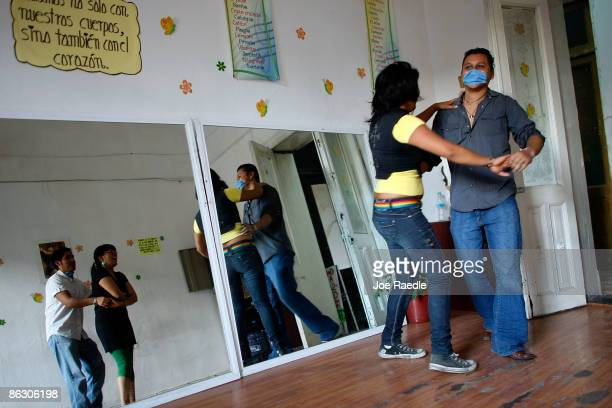 Gabriela Sanchez Contieros and Manuel Alejandro wear surgical masks while dancing to avoid swine flu contamination after the government has advised...