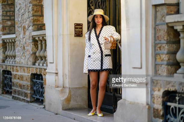 Gabriella Berdugo wears a beige straw hat from Estree a black and white oversized blazer double breasted jacket / dress with printed polka dots from...