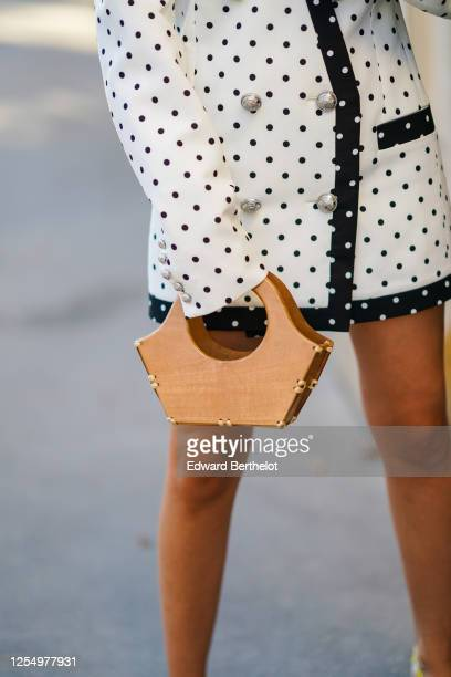Gabriella Berdugo wears a black and white oversized blazer double breasted jacket / dress with printed polka dots from Balmain a wooden bag on July...
