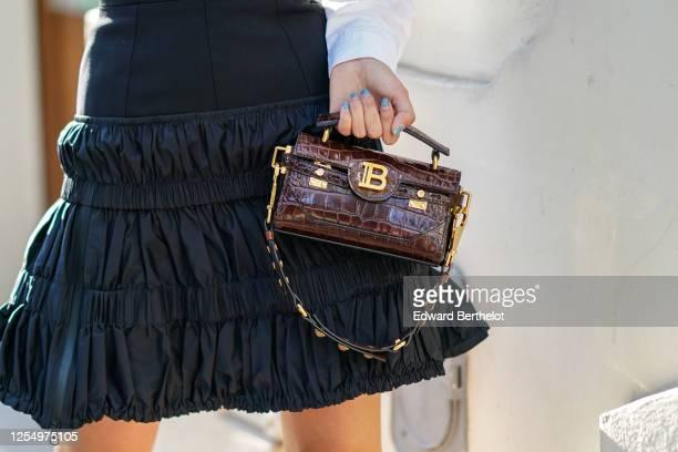 Gabriella Berdugo wears a black ruffled pleated dress from Mugler, a brown leather Balmain with crocodile pattern, on July 07, 2020 in Paris, France.