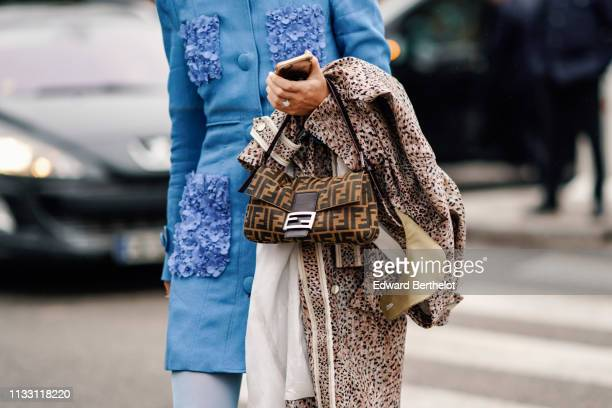Gabriella Berdugo wears a blue tunic with pockets decorated with blue textile flowers a Fendi bag a leopard print trench coat outside Nina Ricci...