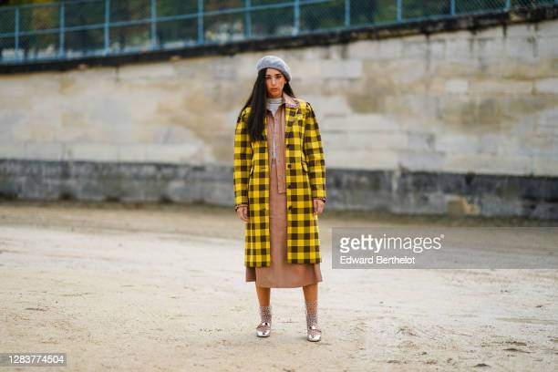Gabriella Berdugo wears a gray beret hat, a yellow and brown checkered long coat, a salmon-pink dress, a gray pullover, mesh polka dots socks, silver...