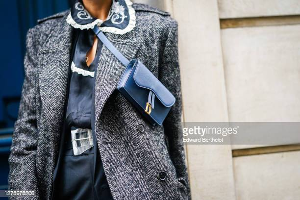 Gabriella Berdugo wears a gray long wool coat, a blue Dior small bag, a black dress with white ruffled collar and floral embroidery, a belt, outside...