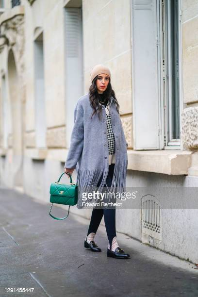 Gabriella Berdugo wears a gray wool coat with fringes from Dorothee Schumacher, a beige beanie hat, black legging with strappy legs, a black and...