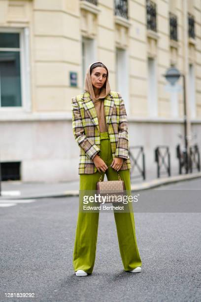 Gabriella Berdugo wears a green and beige checked blazer with beige hoodie knit jumper and green high waisted palazzo pants with belt, printed...