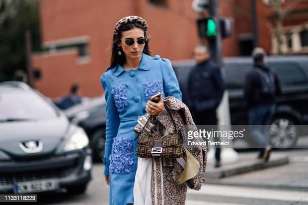 Gabriella Berdugo wears a leopard print headband, sunglasses, earrings, a blue tunic with pockets decorated with blue textile flowers, a Fendi bag, a...