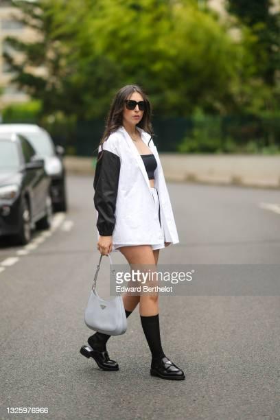 Gabriella Berdugo wears a Prada full look: an oversized black and white shirt, a black cropped top, sponge towel shorts, black long socks, black...