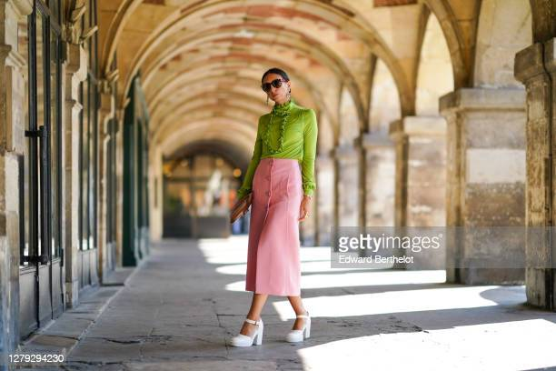 Gabriella Berdugo wears a total look Prada, a green ruffle blouse with long sleeves, a pink pencil midi skirt with pockets, a brown leather pouch /...