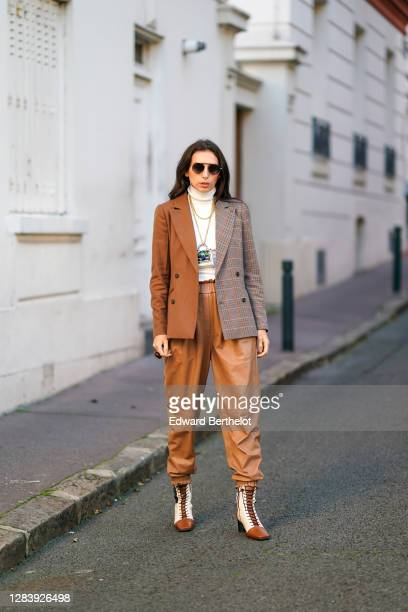 Gabriella Berdugo wears beige leather sweat pants jogger from Munthe, a white turtleneck wool pullover from Munthe, a bicolor brown and gray checked...