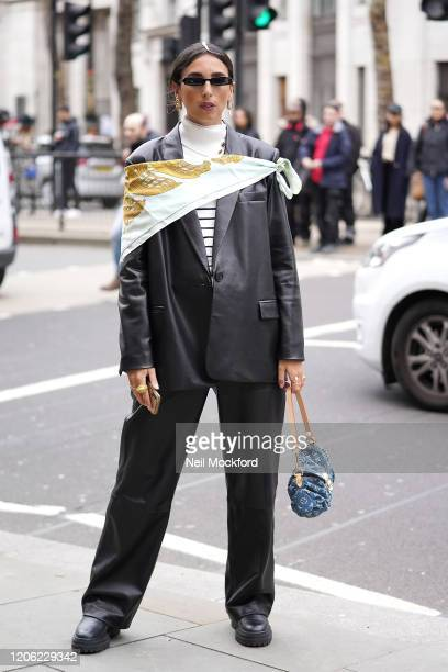 Gabriella Berdugo wears black leather jacket and trousers with printed scarf and Louis Vuitton purse during London Fashion Week February 2020 on...