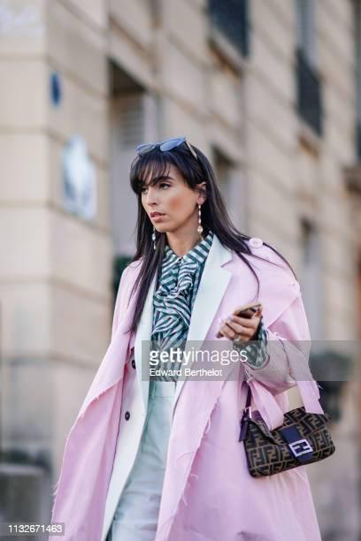 Gabriella Berdugo wears earrings sunglasses a pink coat a black and white striped shirt flared pants green shoes a Fendi bag outside Dries Van Noten...