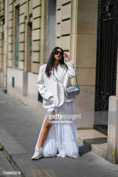 Gabriella Berdugo wears JW Anderson x Converse sneakers shoes, a blue and white striped bag from Staud, Gucci sunglasses, a white oversized blazer...