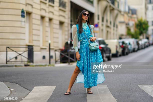 Gabriella Berdugo wears Moncler sunglasses, a Maje green shirt with puff mesh sleeves, a Maje bold blue flowing dress with water pattern print, a...