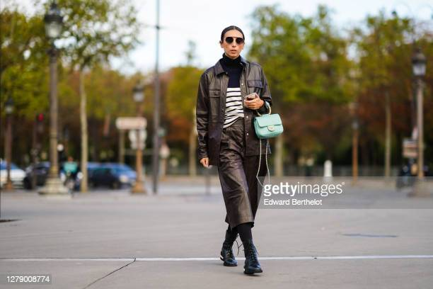 Gabriella Berdugo wears sunglasses, a black and white striped pullover with turtleneck, a brown leather oversized jacket, a pale green Chanel bag,...