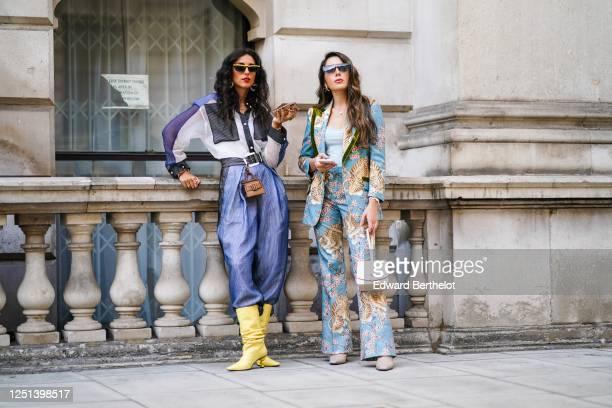 Gabriella Berdugo wears sunglasses, a blue and white shirt, a brown leather belt bag, blue pants, yellow pointy boots ; Nurce Erben wears sunglasses,...