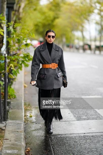 Gabriella Berdugo wears sunglasses, a gray oversized Prada coat, an orange large belt, a fringed skirt, black pants, leather boots, outside Louis...