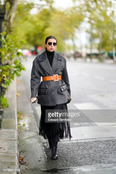 Gabriella Berdugo wears sunglasses, a gray oversized Prada coat, an orange large belt, a fringed skirt, black pants, leather boots, outside Louis...