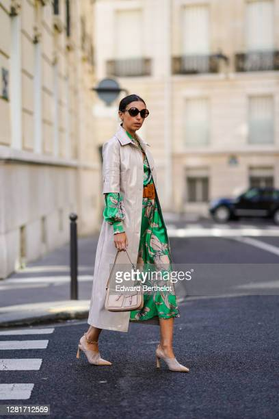 Gabriella berdugo wears sunglasses, a green floral printe silky midi skirt co ord with blouse , a long leather with mid sleeve beige jacket, mesh...
