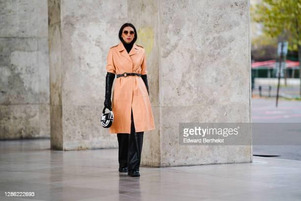 Gabriella Berdugo wears sunglasses, a peach-beige long leather trench coat, a black turtleneck pullover, black leather long gloves, a black leather...