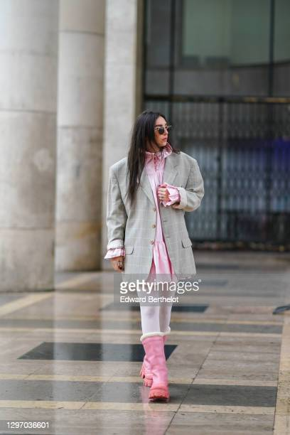 Gabriella Berdugo wears sunglasses, a pink ruffle dress with collar from Avavav, a beige vintage oversized blazer jacket with checked print, white...