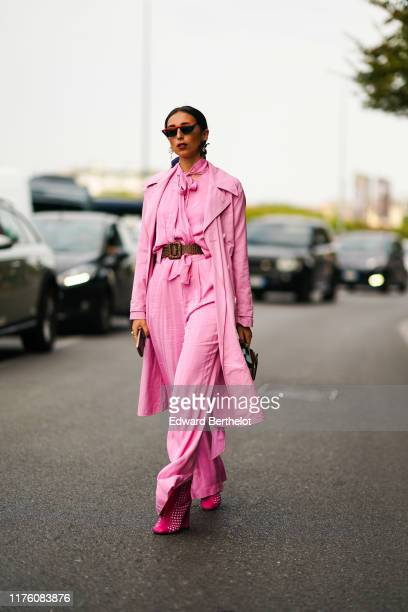 Gabriella Berdugo wears sunglasses, a pink trench coat, a pink flowing shirt, flared pants, pink shoes, a brown and pale green bag, a brown leather...
