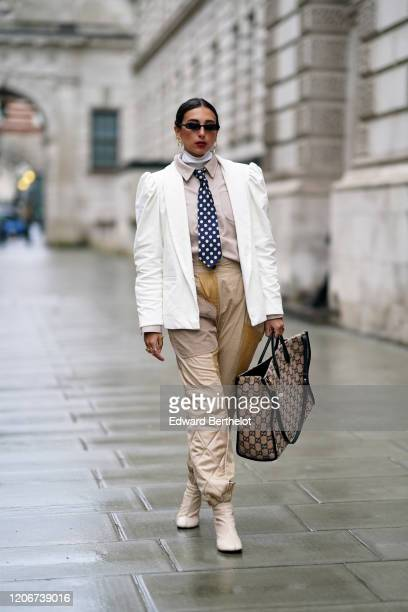 Gabriella Berdugo wears sunglasses a white jacket with shoulder pads a shirt a blue tie with white polka dots quilted pants white boots a Gucci...