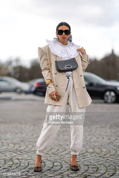 Gabriella Berdugo wears sunglasses, a white ruffled shirt, a beige oversized blazer jacket, a golden bracelet, finger rings, a Dior Saddle bag, white...