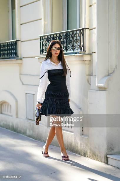 Gabriella Berdugo wears sunglasses a white shirt a black ruffled pleated dress from Mugler a brown leather Balmain with crocodile pattern Balenciaga...