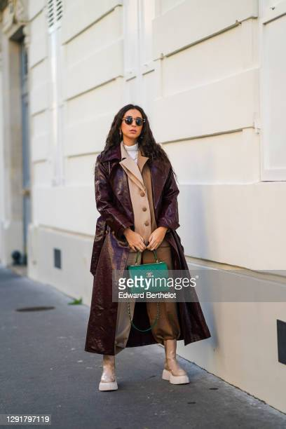 Gabriella Berdugo wears sunglasses, a white turtleneck pullover, earrings, a necklace, a bi color beige and brown oversized blazer jacket and suit...