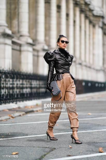 Gabriella Berdugo wears sunglasses earrings a black leather ruffled jacket with puff shoulder pads a Dior monogram logo bag brown leather pants mesh...