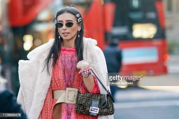 Gabriella Berdugo wears sunglasses earrings a pink and orange mesh floral print mesh dress a Fendi bag a white fluffy coat sneakers during London...