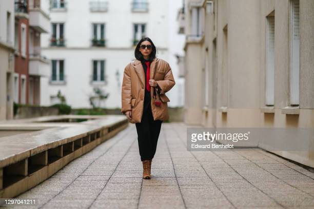 Gabriella Berdugo wears sunglasses from Cazal, a beige leather puffer oversized coat from Prada, a red tie and a black shirt from Prada, black...