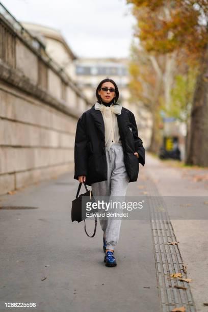 Gabriella Berdugo wears sunglasses from Ralph Lauren, a black puffed winter oversized jacket from Prada, beige organza blouse shirt with Lavallière...