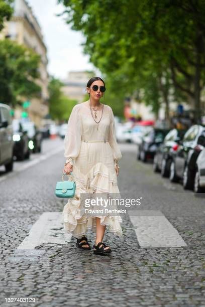 Gabriella Berdugo wears sunglasses, gold chain for sunglasses, gold earrings, silver and gold chain pendant necklaces, a white lace tank-top, a long...