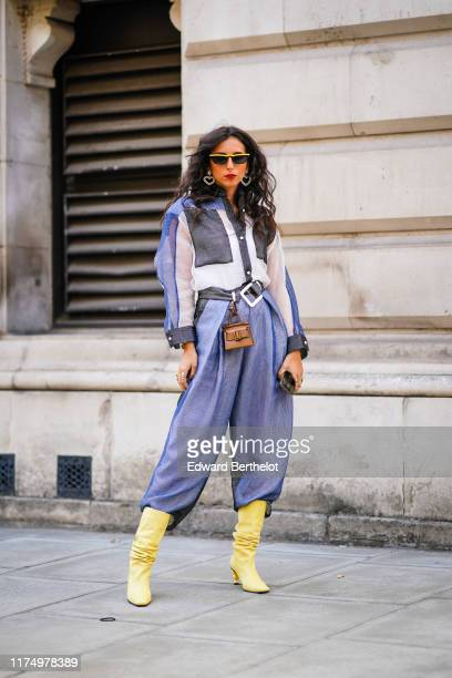 Gabriella Berdugo wears yellow sunglasses heart shaped earrings a blue white and black shirt blue pants yellow boots a belt with an attached mini...