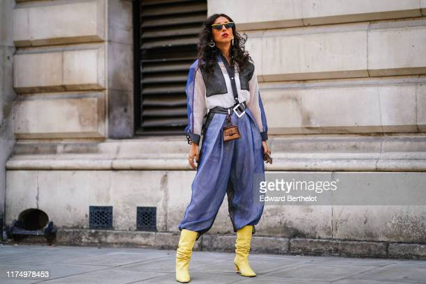 Gabriella Berdugo wears yellow sunglasses, heart shaped earrings, a blue white and black shirt, blue pants, yellow boots, a belt with an attached...