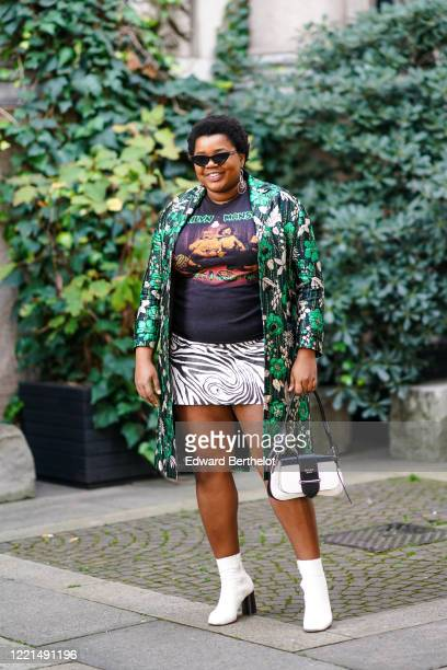 Gabriella Karefa-Johnson wears sunglasses, earrings, a green long floral print coat, an Iron Maiden t-shirt, a black and white zebra print short...